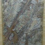 """Zbytky německé mapy nalezené při pátrání v akci """"Zdeňka"""". Mapa je zasazena do skleněné desky."""